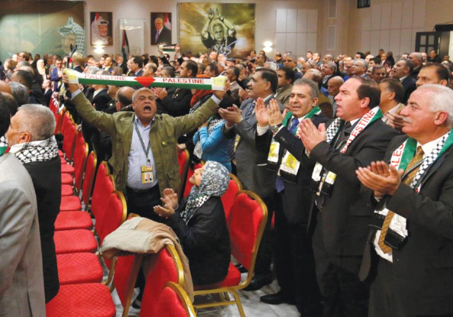 PARTICIPANTS CLAP and cheer before a speech by Palestinian Authority President Mahmoud Abbas during