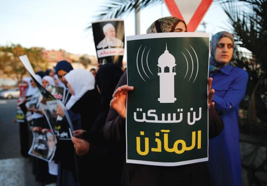 PROTESTERS AGAINST a law that would lower the volume of mosque loudspeakers hold a sign in Umm el-Fa