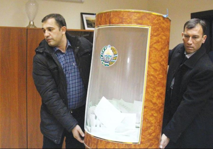 MEMBERS OF a local electoral commission carry a ballot box after the presidential election in Tashke
