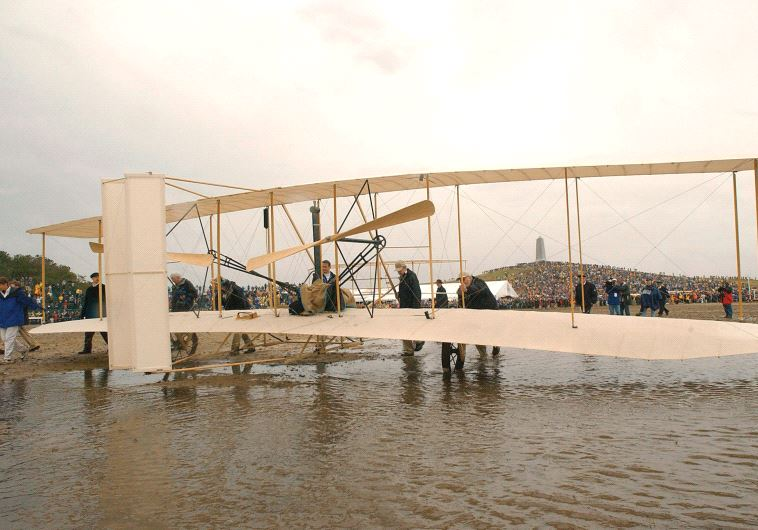 THE WRIGHT EXPERIENCE team rolls a Wright 1903 Flyer replica onto the field at the Wright Brothers N