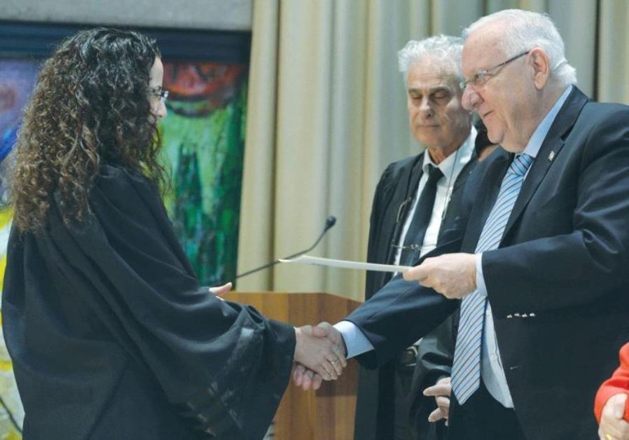 PRESIDENT REUVEN RIVLIN speaks with Jerusalem Magistrate's Court Judge Miriam Banki yesterday, as Na