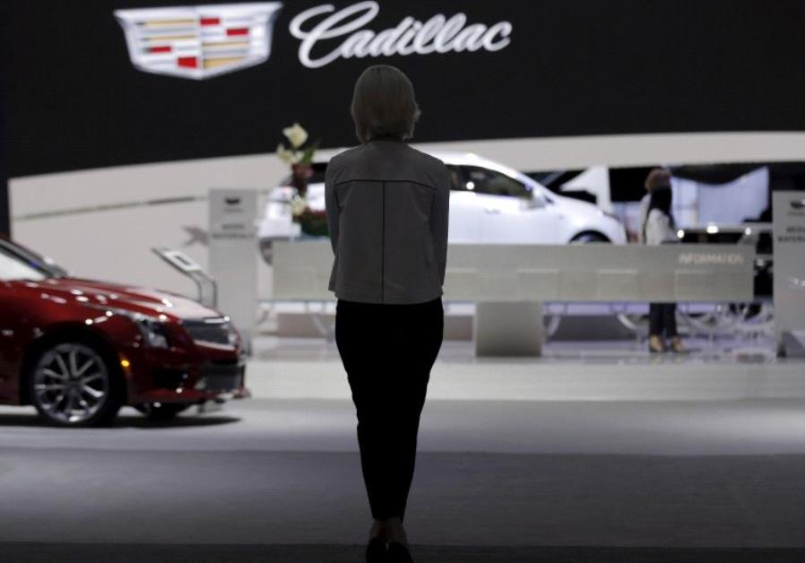 A woman stands in the Cadillac exhibit at the New York International Auto Show media preview in Manh