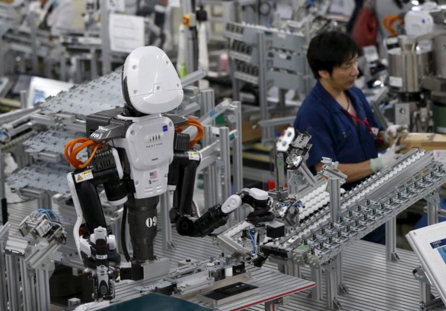 A humanoid robot works side by side with employees in the assembly line at a factor