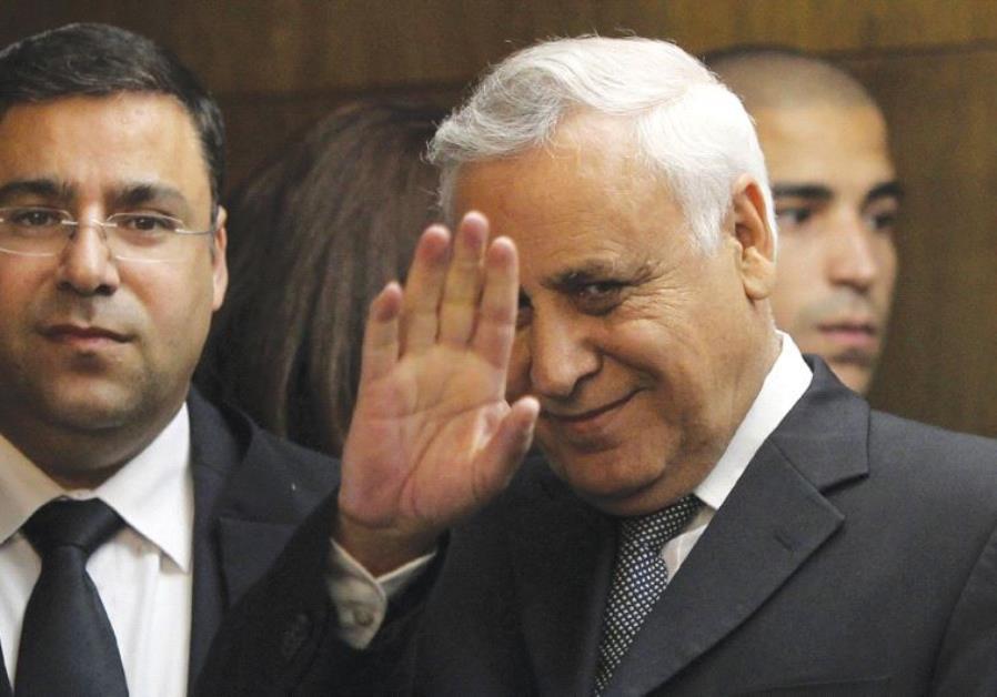 FORMER PRESIDENT Moshe Katsav waves to the press as he enters Tel Aviv District Court on December 30