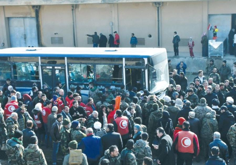 PEOPLE WAIT for buses after being displaced by fighting near Aleppo in Syria