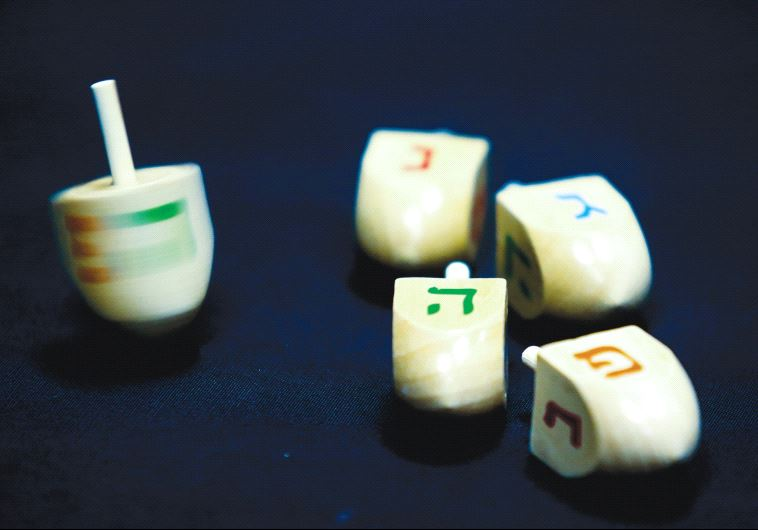 HANUKKA DREIDELS display the letters of the Hebrew acronym for 'A great miracle happened here.'