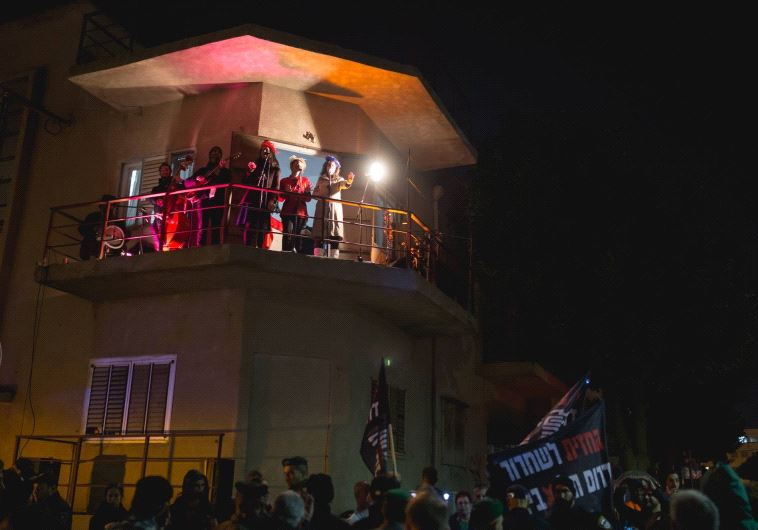 Anti-immigrant protestors wave flags as Christmas carolers sing from a balcony in the Neve Sha'anan