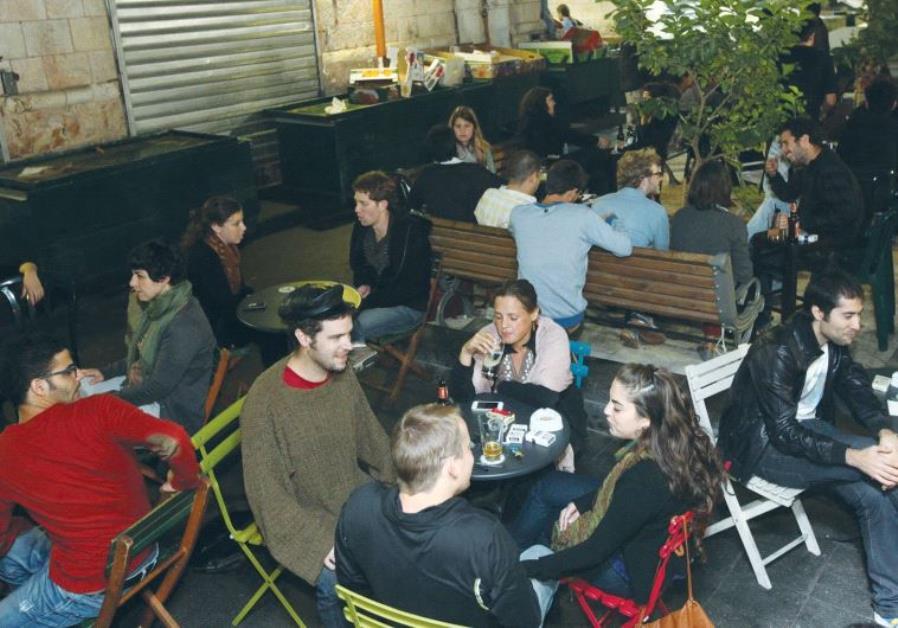 PEOPLE DRINK at Jerusalem's Casino de Paris bar, something