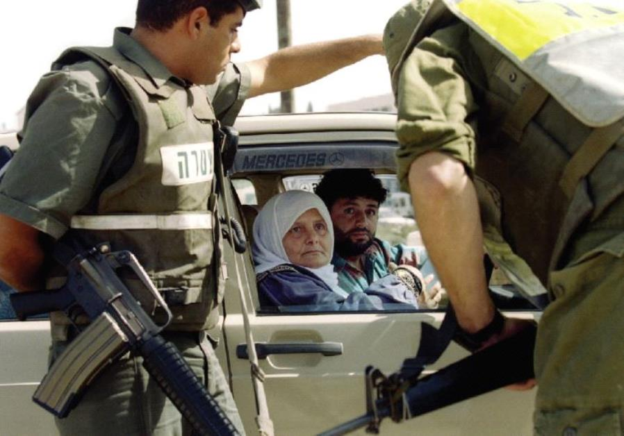 SOLDIERS AND Border Police question a Palestinian couple at a roadblock leading from the West Bank i