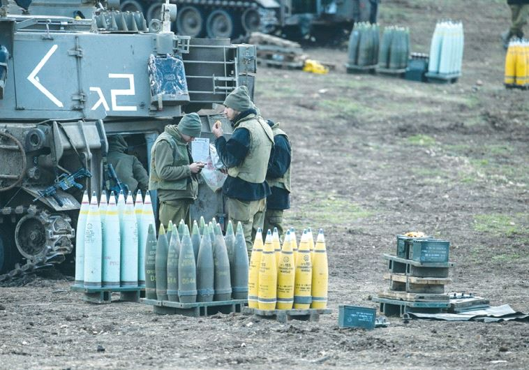IDF SOLDIERS stand next to ammunition and a mobile artillery unit near the border with Syria last ye