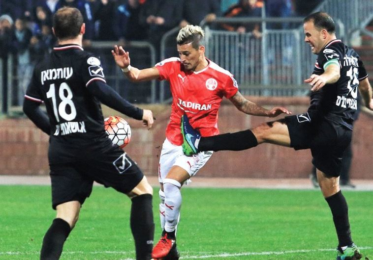 Hapoel Beersheba midfielder Maor Buzaglo (center) was frustrated by Bnei Sakhnin's Khaled Khalaila (