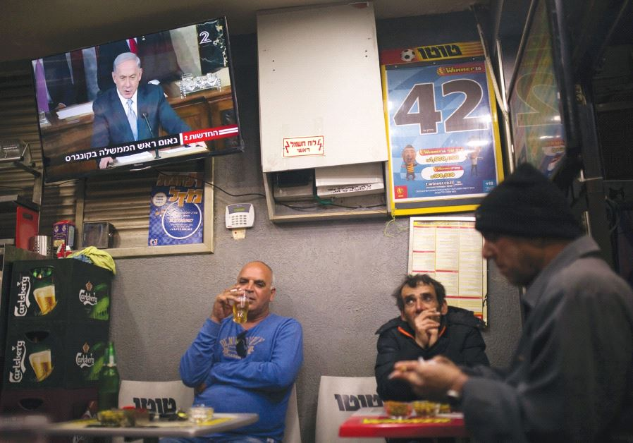 PEOPLE SIT at a kiosk in Ashkelon as a television broadcasts Prime Minister Benjamin Netanyahu's spe