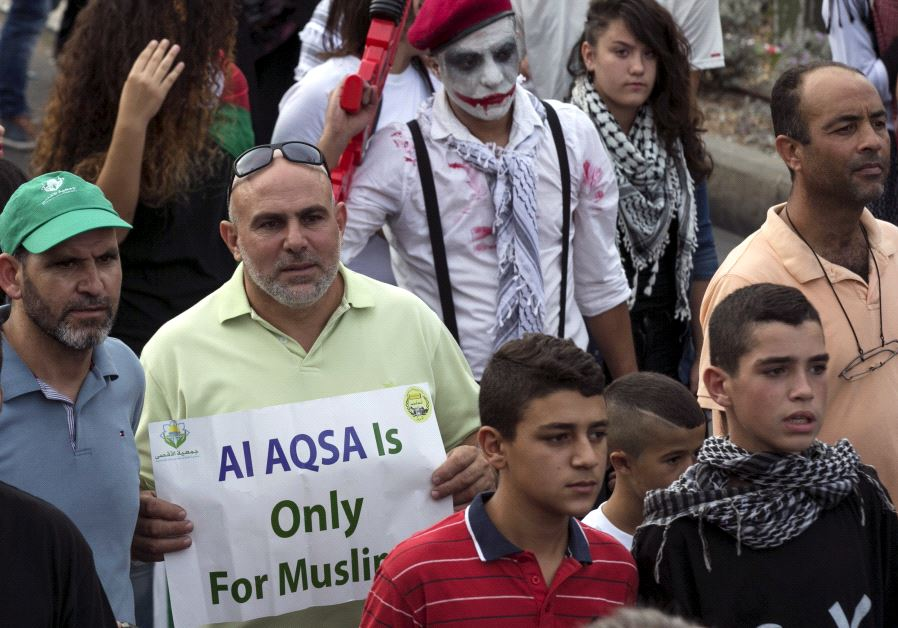 """Israeli Arabs take part in a pro-Palestinian rally. One protester holds a sign stating """"Al-aqsa [Tem"""