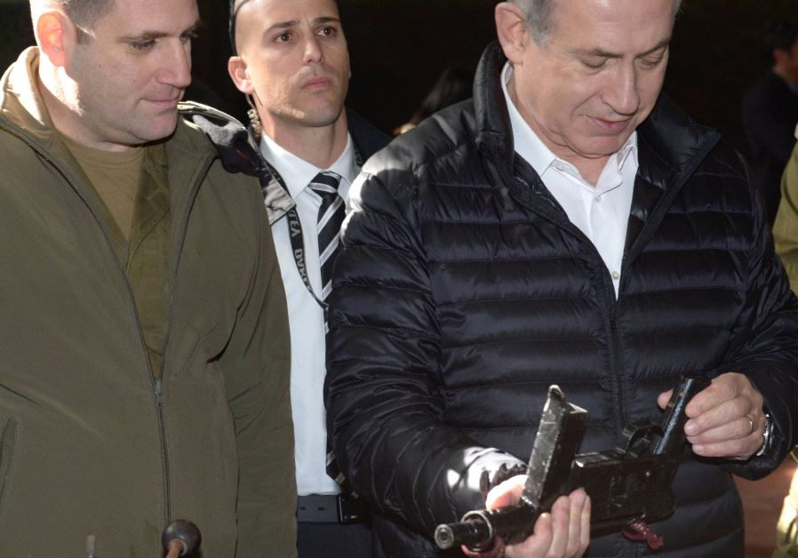 Prime Minister Benjamin Netanyahu examines a firearm during a visit to the West Bank