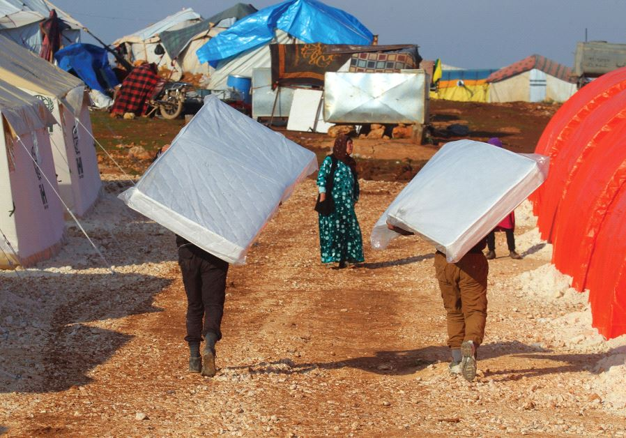 EVACUEES from a rebel-held area of Aleppo carry mattresses they received in the Kamouneh camp in Syr