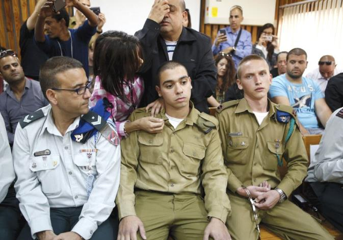 THE FATHER of convicted Sgt. Elor Azaria (center) prays behind him in a military court during a rema