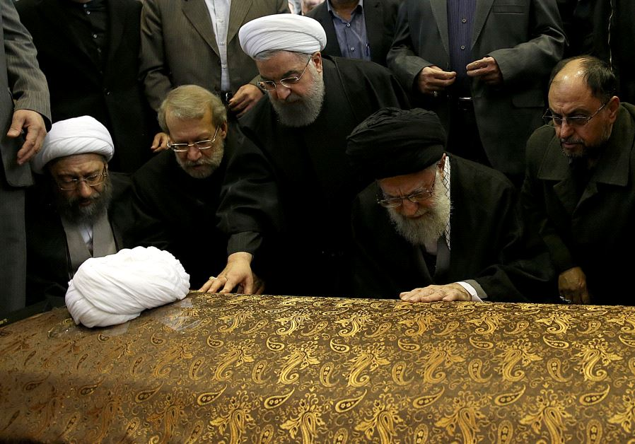 Iran's Supreme Leader Ayatollah Ali Khamenei and Iran's President Hassan Rouhani touch the coffin of