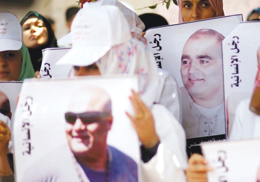 PALESTINIANS HOLD POSTERS of Mohammad El Halabi, World Vision's manager of operations in the Gaza St