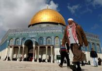 Palestinians walk past the Dome of Rock at the Al-Aqsa Mosque compound in Jerusalem's Old City, on J