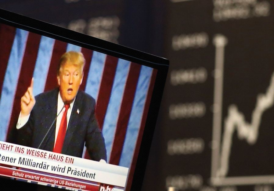 A TV SCREEN showing President-elect Donald Trump is pictured in front of the German share price inde