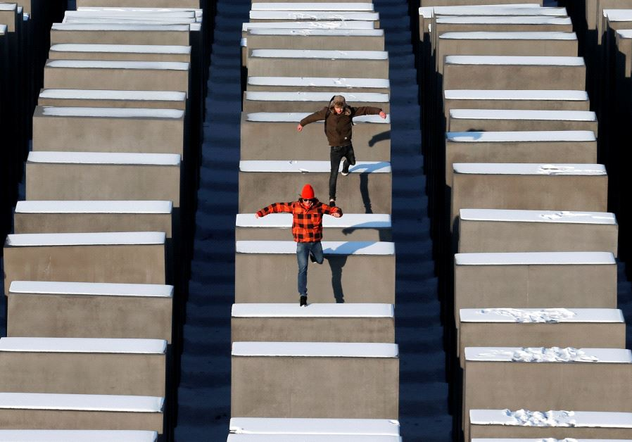 People jump from concrete elements of the Holocaust memorial in Berlin