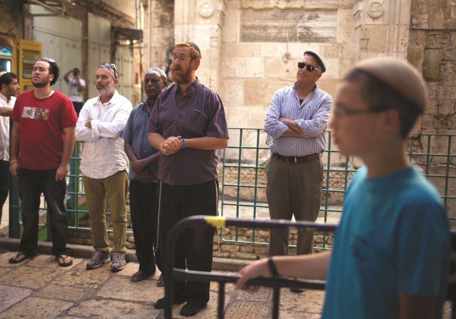 Yehouda Glick (au centre) priant à l'extérieur de l'enceinte du mont du Temple avec quelques fidèles