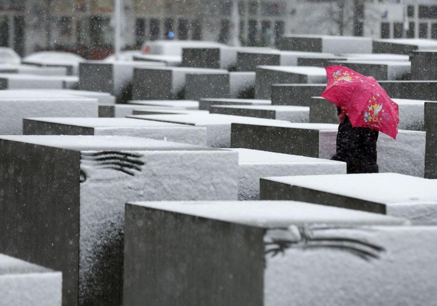 A woman walks through the Holocaust memorial during heavy snowfall in Berlin