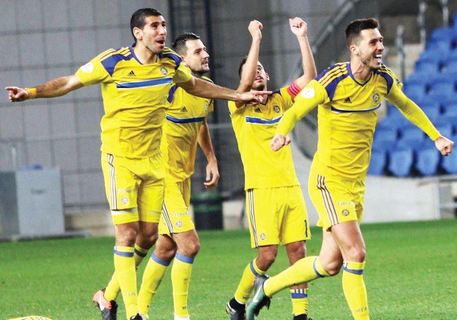 Maccabi Tel Aviv players celebrate last night in Netanya after clinching victory over Hapoel Ra'ana