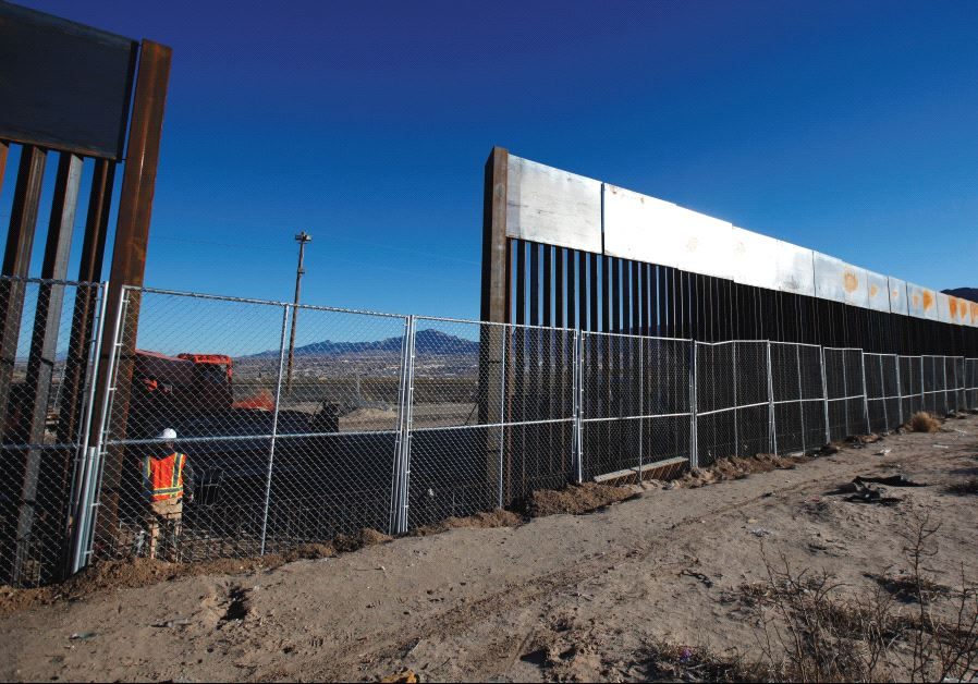 A WORKER STANDS next to a newly built section of the US border fence at Sunland Park, New Mexico.