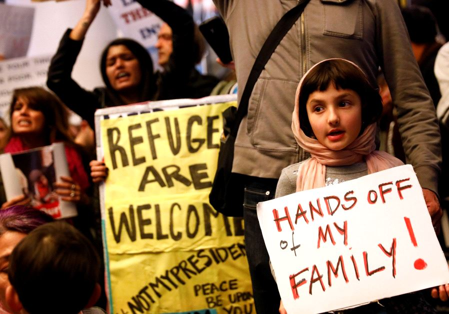 holds a sign in support of Muslim family members as people protest against U.S. President Donald Tru