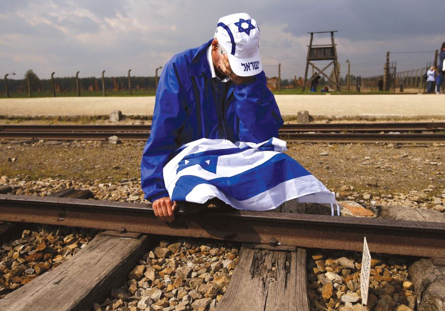 A man sits on the railway tracks in the former Nazi death camp of Auschwitz-Birkenau as thousands of