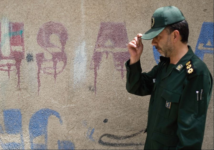 A MEMBER of Iran's Revolutionary Guard walks past anti-US graffiti at a ceremony in 2008.