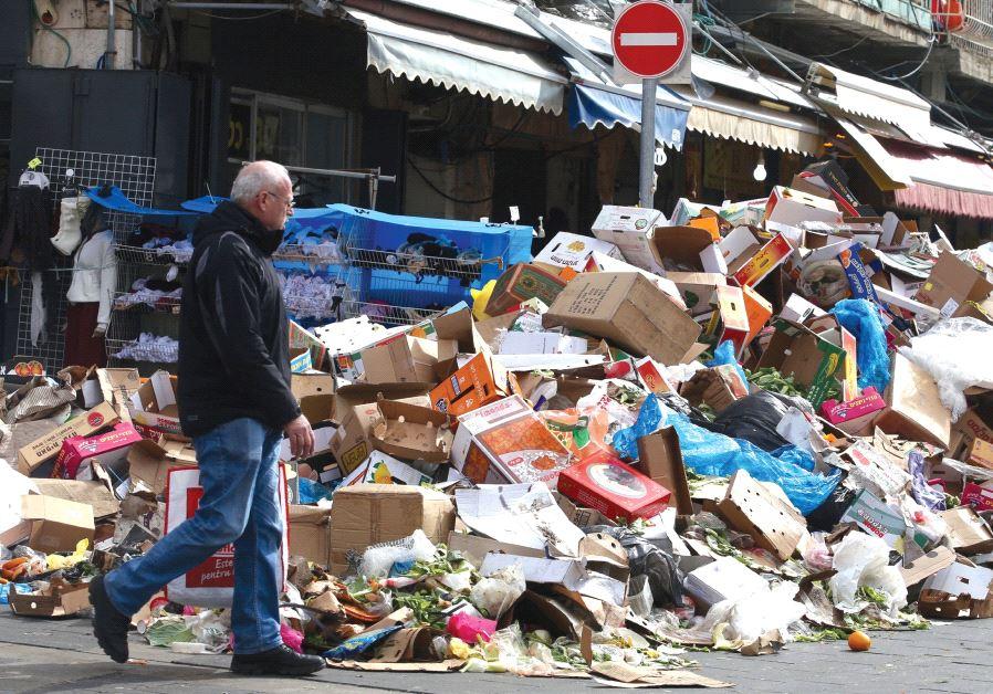 A MAN walks past a heap of garbage outside Jerusalem's Mahaneh Yehuda Market during the three-day mu