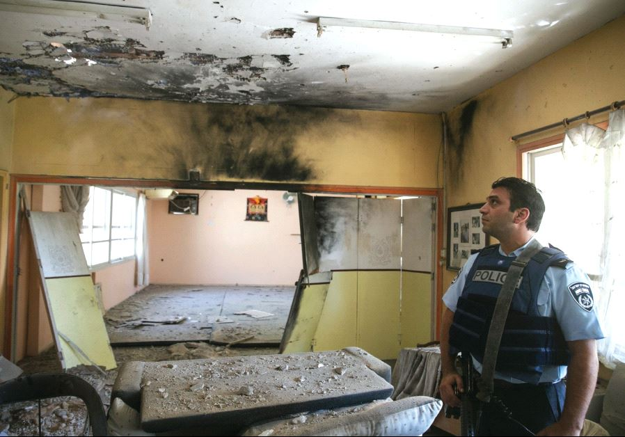 A POLICEMAN surveys a building damaged from a Palestinian mortar.