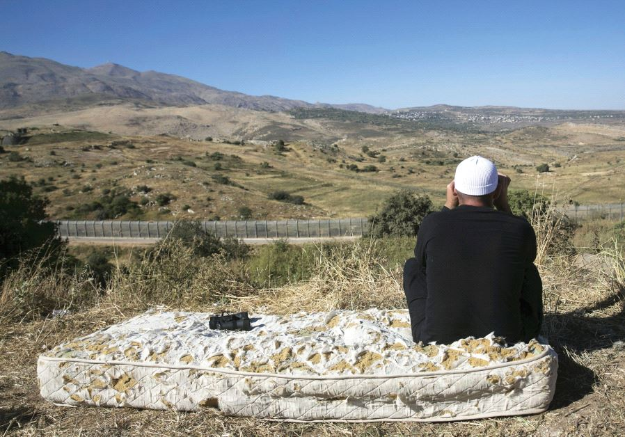 A DRUSE man watches the fighting in Syria from the Israeli side of the Golan Heights