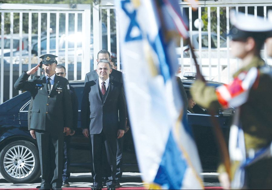 TURKISH AMBASSADOR Kemal Okem stands at attention for the Turkish national anthem before presenting