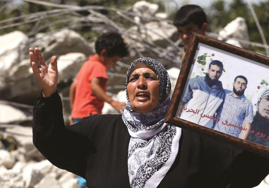 Une mère brandissant la photo de ses enfants, auteurs d'attentats