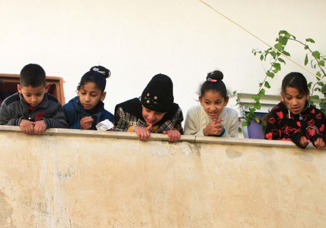 Children look out of the family house of Palestinian Mohammad Al-Salahe, 32, in Al-Faraa refugee cam