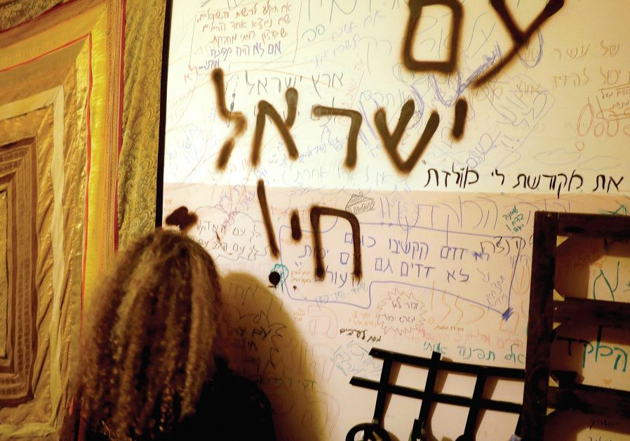 A WOMAN stands next to a wall covered in graffiti inside a home in Amona on February 1.