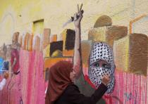 A Palestinian woman paints a mural, depicting a masked Palestinian holding a knife, in support of Pa