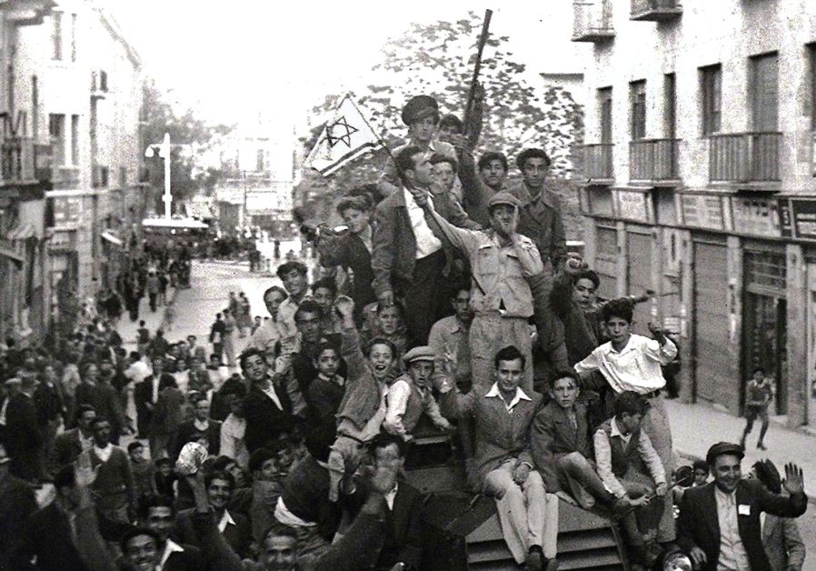 JEWS CROWD onto a British army armored car as they celebrate in downtown Jerusalem the morning after