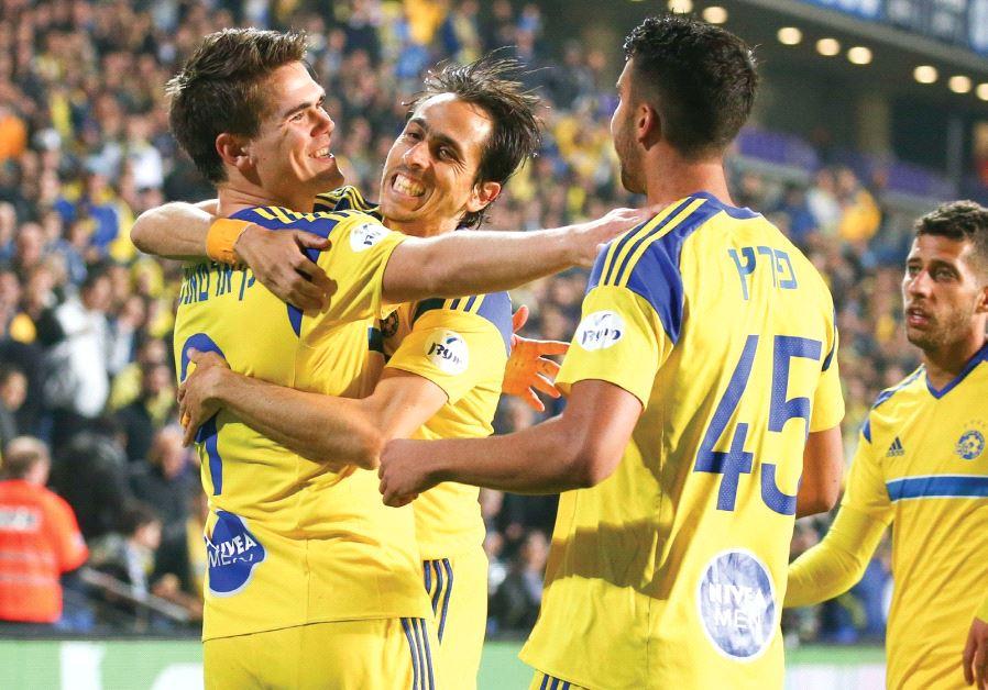 Vidar Orn Kjartansson (left) celebrates with teammates Yossi Benayoun (center) and Eliel Peretz afte
