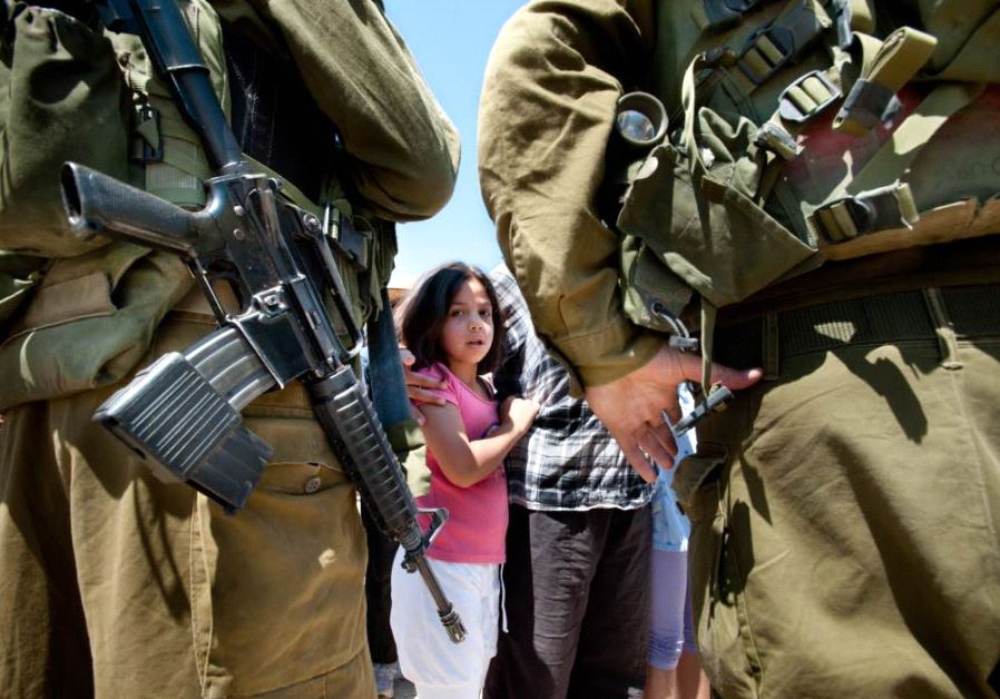 Israeli soldiers next to a Palestinian girl as displayed in the report.