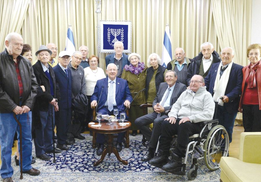 PRESIDENT REUVEN RIVLIN sits in the center of former Lehi members and others marking 75 years since