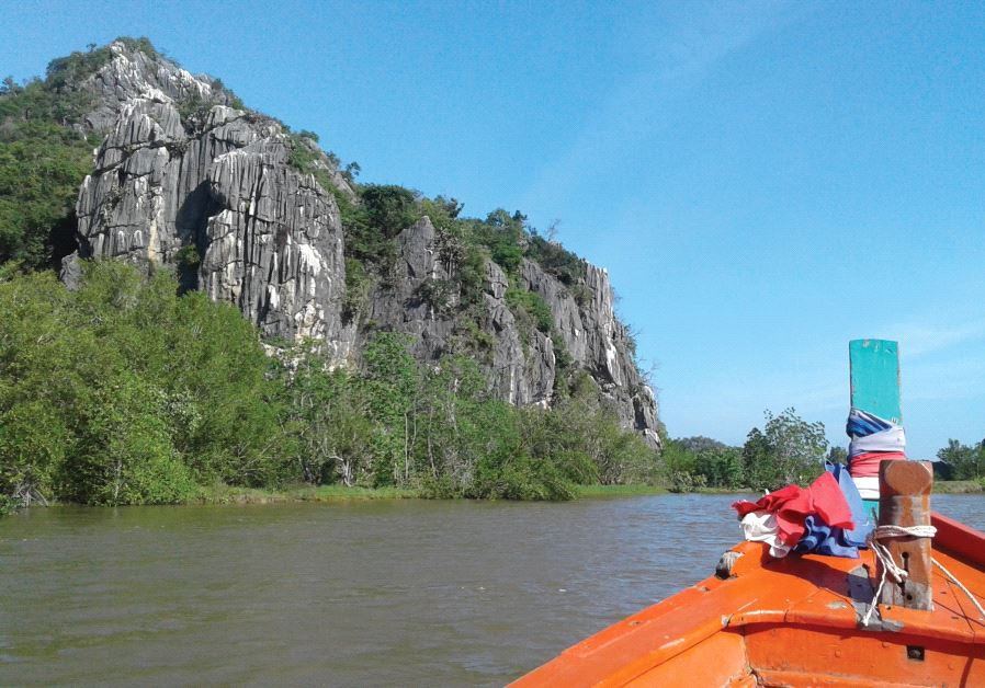 THE PROW of our boat points down between the mountains on both sides of the Pretchaburi River