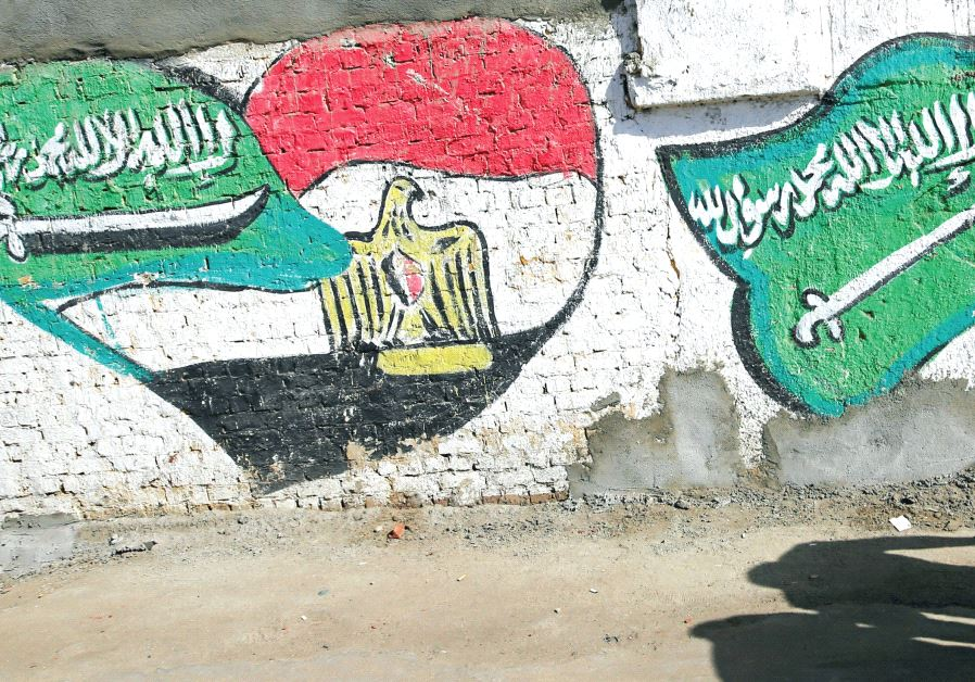 THE SHADOWS of men walking are seen in front of graffiti depicting relations between Egypt and Saudi