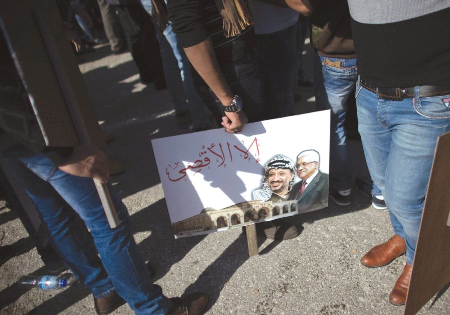 PALESTINIANS STAND next to a portrait of the Palestinian Authority President Mahmoud Abbas and the l