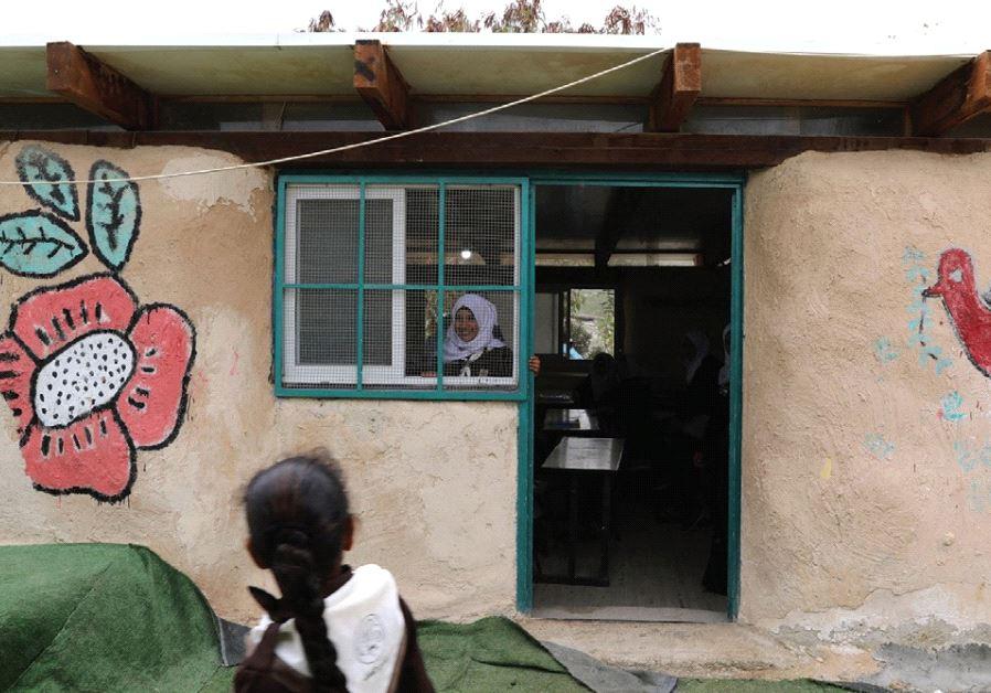 A BEDUIN SCHOOLGIRL looks out the window of her classroom at the Al-Khan al-Ahmar school.