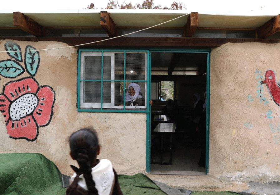A BEDUIN SCHOOLGIRL looks out the window of her classroom at the Al-Khan al-Ahmar school.