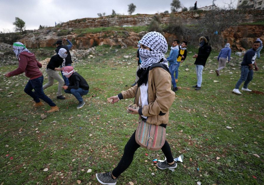 A female Palestinian protester holds stones during clashes with Israeli troops near Israel's Ofer Pr
